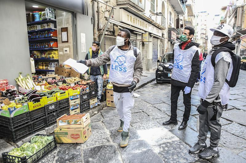 A group of migrants, who collaborate as volunteers with the Less cooperative, bring bags of food and medicine to the home of older people, or who cannot go shopping, due to government restrictions or for fear of coronavirus infection. | Roberta Basile—KONTROLAB/LightRocket/Getty Images