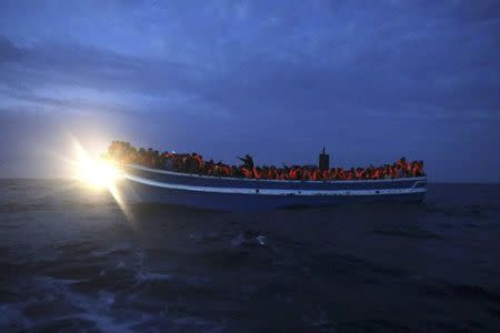 Migrants are seen onboard a drifting overcrowded wooden boat, during a rescue operation by the Spanish NGO Proactiva Open Arms, north of the Libyan city of Sabratha in central Mediterranean Sea