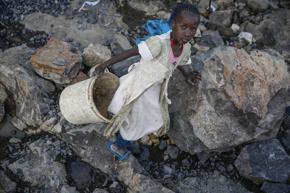 Irene Wanzila, 10, carries a bucket of broken rocks after breaking them with a hammer along with her younger brother, older sister and mother, who says she was left without a choice after she lost her cleaning job at a private school when coronavirus pandemic restrictions were imposed, at Kayole quarry in Nairobi, Kenya Tuesday, Sept. 29, 2020. The United Nations says the COVID-19 pandemic risks significantly reducing gains made in the fight against child labor, putting millions of children at risk of being forced into exploitative and hazardous jobs, and school closures could exacerbate the problem. (AP Photo/Brian Inganga)