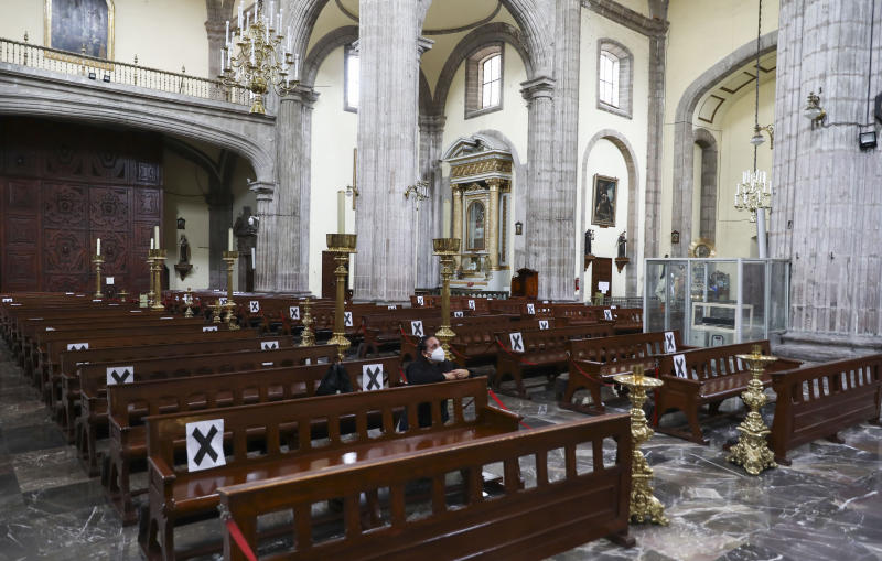 A woman wearing a mask to curb the spread of the new coronavirus prays inside a church in Mexico City, Monday, June 29, 2020. Mexico City is moving this week to the next stage of its gradual reopening from its COVID-19 pandemic lockdown. (AP Photo/Eduardo Verdugo)