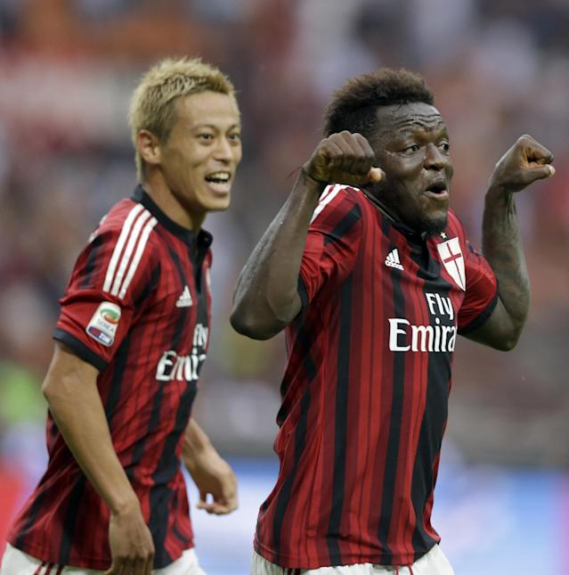 AC Milan midfielder Sulley Muntari, of Ghana, right, celebrates flanked by his teammate forward Keisuke Honda after scoring his side's second goal, during a Serie A soccer match between AC Milan and Lazio, at the San Siro stadium in Milan, Italy, Sunday, Aug. 31, 2014. (AP Photo/Luca Bruno)
