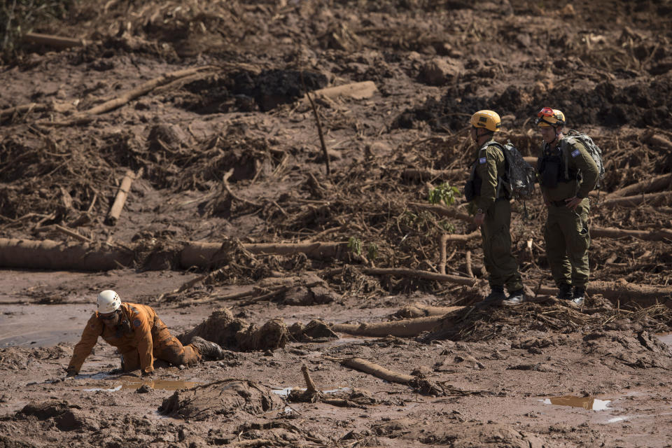 A Brazilian firefighter, left, crawls over the mud as Israeli rescue specialists stand look on, after a dam collapse in Brumadinho, Brazil, Monday, Jan. 28, 2019. Firefighters on Monday carefully moved over treacherous mud, sometimes walking, sometimes crawling, in search of survivors or bodies four days after a dam collapse that buried mine buildings and surrounding neighborhoods with iron ore waste. (AP Photo/Leo Correa)