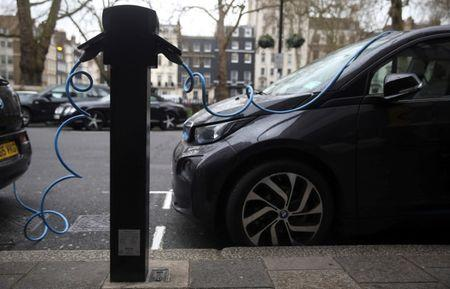 FILE PHOTO: Electric cars are plugged into a charging point in London