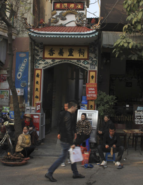 In this Jan. 23, 2014 photo, a man walks by Huong Nghia Temple in the heart of the Old Quarter of Hanoi, Vietnam. With property values high, this neighborhood could change dramatically in the coming years as similar ones already have in Singapore, Shanghai and many other cities. Authorities want to begin gentrifying the Old Quarter by relocating 6,200 households between 2014 and 2020. New construction is likely a few years away, but a few hundred residents already have been relocated. (AP Photo/Mike Ives)
