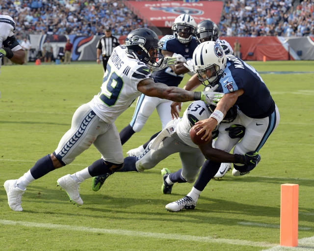 <p>Tennessee Titans quarterback Marcus Mariota (8) reaches for the goal line as he is hit by Seattle Seahawks defenders Earl Thomas (29) and Kam Chancellor (31) in the first half of an NFL football game Sunday, Sept. 24, 2017, in Nashville, Tenn. The play was called back because of a penalty. (AP Photo/Mark Zaleski) </p>