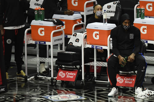 Los Angeles Clippers forward Kawhi Leonard watches the game from the bench during the first half of an NBA basketball game against the Dallas Mavericks in Los Angeles Sunday, Dec. 27, 2020. (AP Photo/Kyusung Gong)