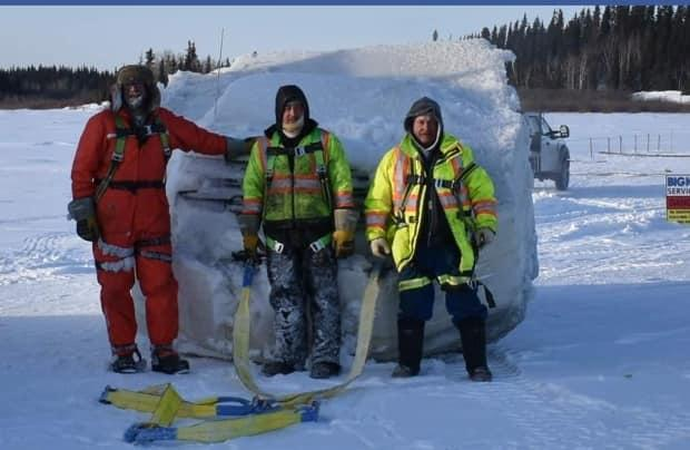 Brett Wildman, left, Dennis Laird, centre, and Dale Buick worked to bring the truck out of the river.