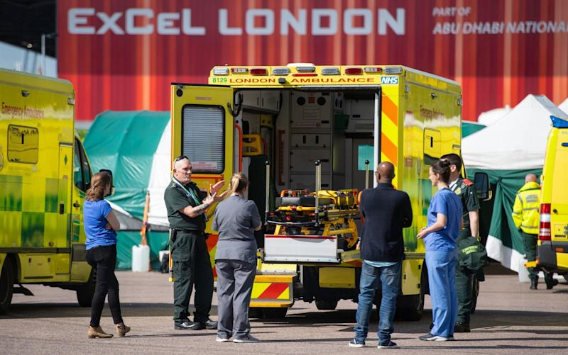 Paramedics and medical staff outside the NHS Nightingale Hospital at the ExCel centre in London. More patients who have recovered from Covid-19 and have cleared the infection are now still presenting with persistent symptoms - Dominic Lipinski/PA