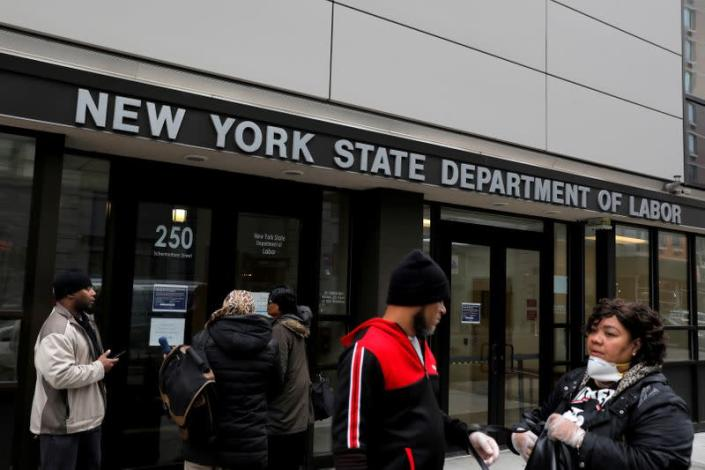 People gather at the entrance for the New York State Department of Labor offices, which closed to the public due to the coronavirus disease (COVID-19) outbreak in the Brooklyn borough of New York City