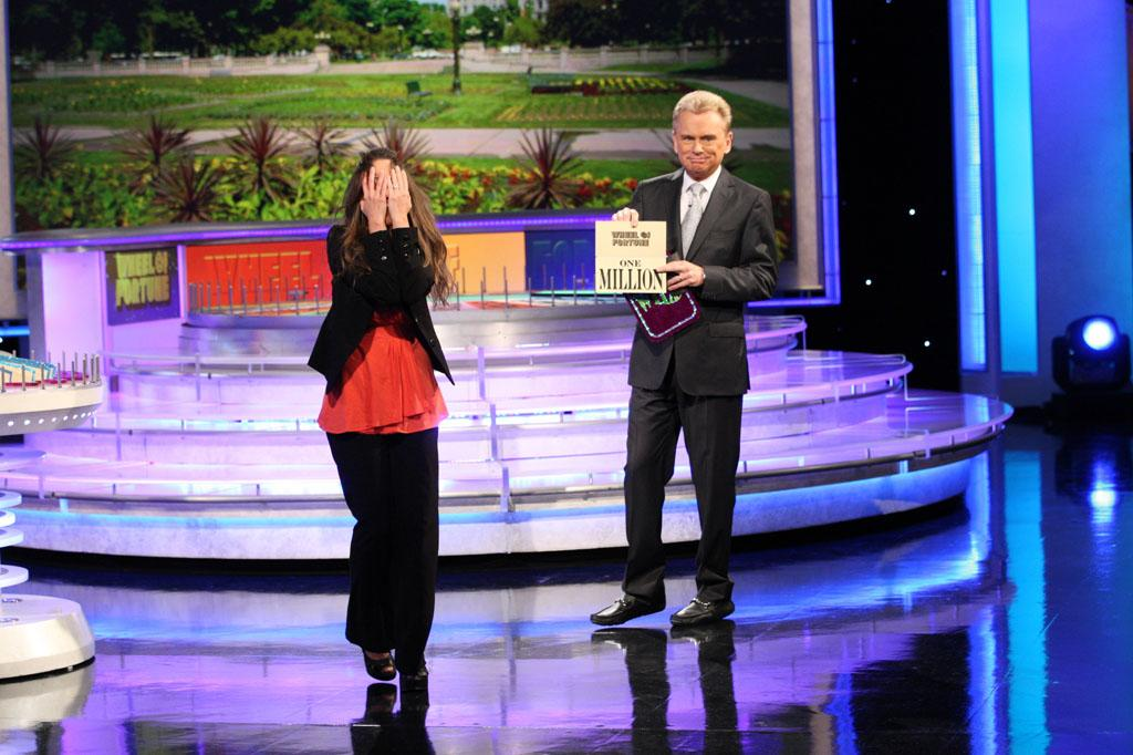 Wheel of Fortune host Pat Sajak opens the bonus round envelope to reveal contestant Autumn Erhard's $1 Million Grand Prize.