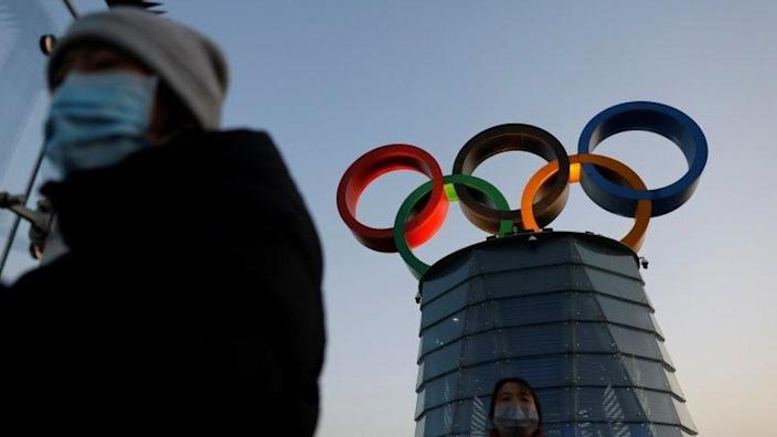 People wearing masks walk by the Olympic Tower in Beijing