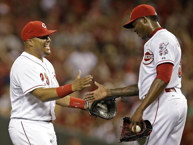Cincinnati Reds' Brayan Pena, left, congratulates relief pitcher Aroldis Chapman after they defeated the Pittsburgh Pirates 6-5 in a baseball game, Friday, July 11, 2014, in Cincinnati. Pena drove in the winning run in the eighth inning and Chapman struck out the side in the ninth inning to earn his 20th save. (AP Photo/Al Behrman)