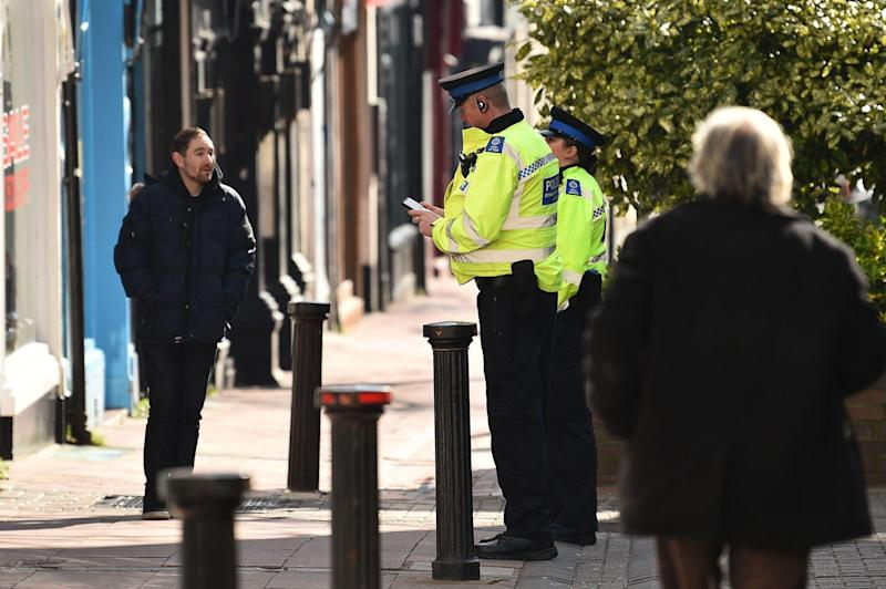 Police community support officers talk to a man on a street in Brighton, southern England on March 24, 2020 after the British government ordered a lockdown to help stop the spread of coronavirus: GLYN KIRK/AFP via Getty Images