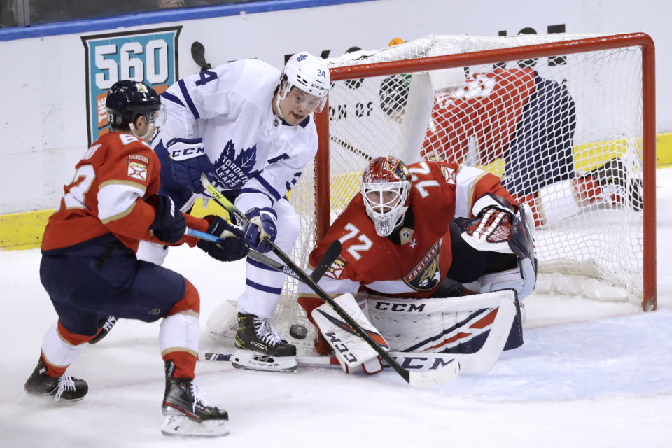 Toronto Maple Leafs center Auston Matthews (34) battles Florida Panthers goaltender Sergei Bobrovsky (72) and right wing Evgenii Dadonov (63) at the net during the second period of an NHL hockey game Thursday, Feb. 27, 2020, in Sunrise, Fla. (AP Photo/Wilfredo Lee)