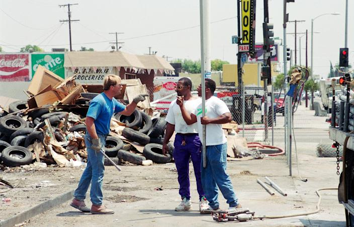 """Armed with metal pipes, a construction worker (in blue) and demonstrators threaten one another during a protest on the northwest corner of the intersection of Florence and Normandie on Aug. 4, 1992. The demonstration was about the lack of Black employees on the job site.<span class=""""copyright"""">Bob Riha, Jr.—Getty Images</span>"""