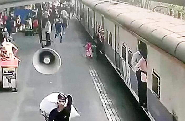 The girl holds her mother's hand as they try to board the train (Picture: SWNS)