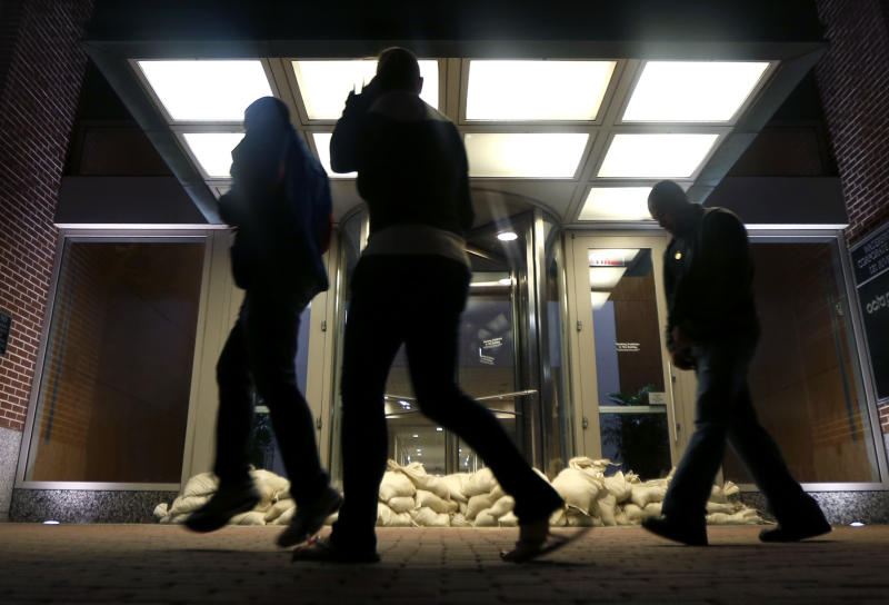 Sandbags line the entrance of a building as people walk by near the Hudson River water front, Sunday, Oct. 28, 2012, in Hoboken, N.J. Tens of thousands of people were ordered to evacuate coastal areas Sunday as big cities and small towns across the U.S. Northeast braced for the onslaught of superstorm Sandy, threatening some 60 million people along the most heavily populated corridor in the nation. (AP Photo/Julio Cortez)