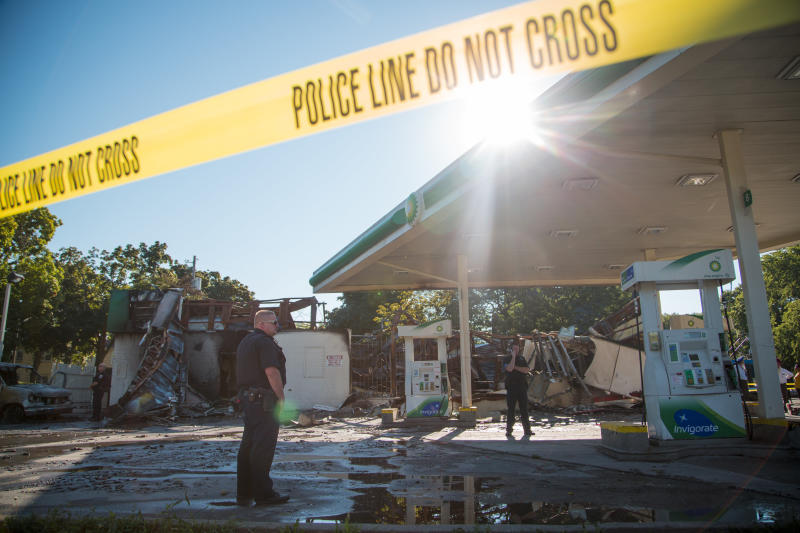 MILWAUKEE, WI - AUGUST 14: A police officer stands guard in front of the damage to the BP gas station after rioters clashed with the Milwaukee Police Department protesting an officer involved killing August 14, 2016 in Milwaukee, Wisconsin. Hundreds of angry people confronted police after an officer shot and killed a fleeing armed man earlier in the day. (Photo by Darren Hauck/Getty Images)