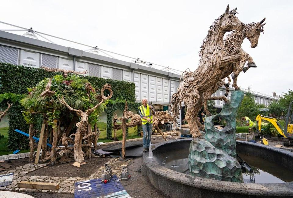 A gardener pressure washes a fountain at the James Doran-Webb Driftwood Sculptures garden ahead of the opening of the flower show (Dominic Lipinski/PA) (PA Wire)