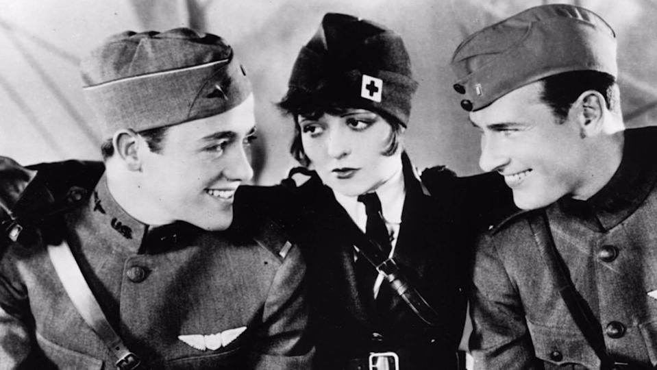 Two men smile at one another as the woman in the middle looks on