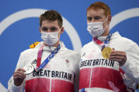 Gold medalist Tom Dean, right, of Britain poses with silver medalist and compatriot Duncan Scott after the men's 200-meter freestyle final at the 2020 Summer Olympics, Tuesday, July 27, 2021, in Tokyo, Japan(AP Photo/Matthias Schrader)