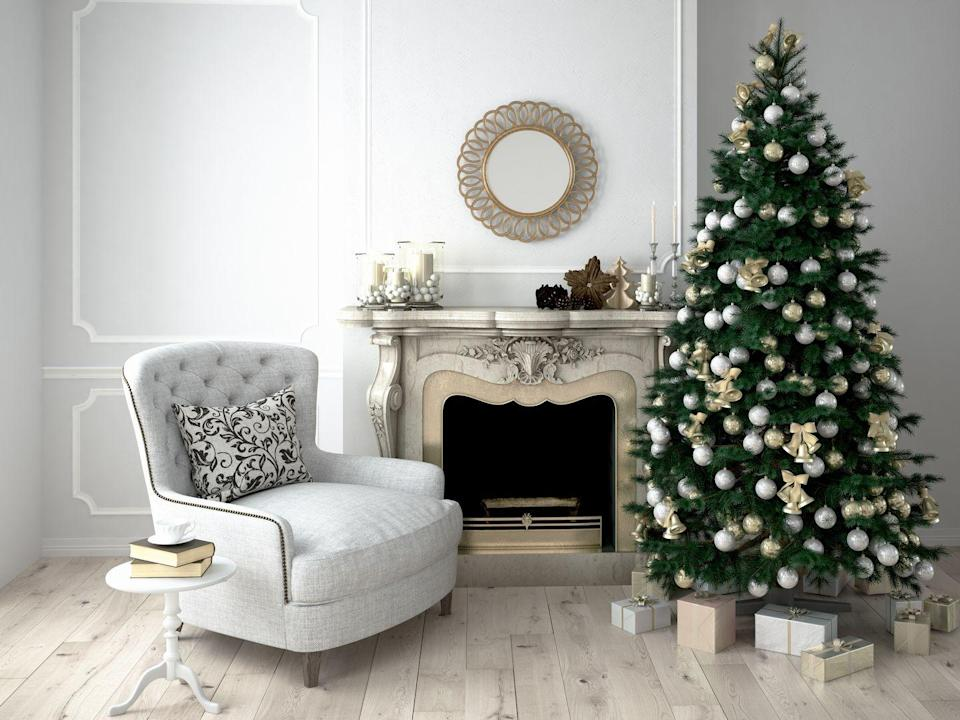 <p>This bright and airy living room features a traditional forest-green pine decorated in a variety of muted and glittery ornaments. The thoughtfully curated decor complements the room's existing design.</p>