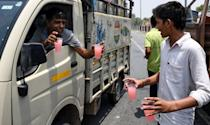 An Indian man distributes free cold sweet water on a highway during a hot afternoon at Garhi village in the northern Indian state of Haryana on June 3, 2019. - Temperatures in an Indian desert city hit 50 degrees Celsius (122 Fahrenheit) for the second time in three days as a deadly heatwave maintained its grip on the country. The thermometer hit 50.3 (122.54 Fahrenheit) in Churu in Rajasthan state, sending residents scrambling for shade to escape the searing sun. (Photo by Money SHARMA / AFP) (Photo credit should read MONEY SHARMA/AFP/Getty Images)
