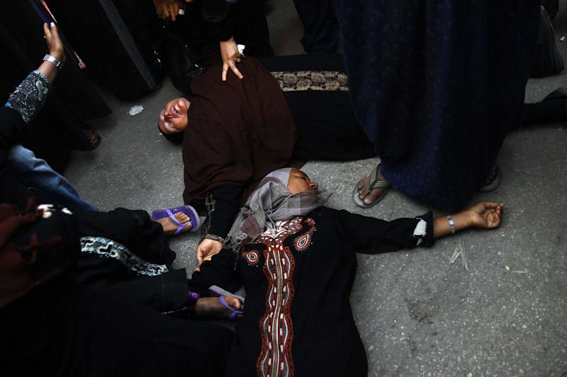 Egyptian women overcome by emotion fall to the ground after a judge sentenced to death more than 680 alleged supporters of the country's ousted Islamist president over acts of violence and the murder of policemen in the latest mass trial in the southern city of Minya, Egypt, Monday, April 28, 2014. Attorney Ahmed Hefni told reporters outside the court in Minya on Monday that the death sentences first have to be approved by Egypt's mufti, the top Islamic official — a step that is usually considered a formality. (AP Photo/Ahmed Gomaa)