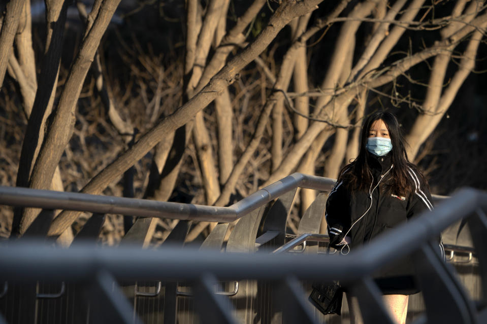 A woman wearing a face mask to protect against the spread of the coronavirus walks along a street during the morning rush hour in Beijing, Wednesday, Dec. 30, 2020. Beijing has urged residents not to leave the city during the Lunar New Year holiday in February, implementing new restrictions and mass testings after several coronavirus infections last week. (AP Photo/Mark Schiefelbein)
