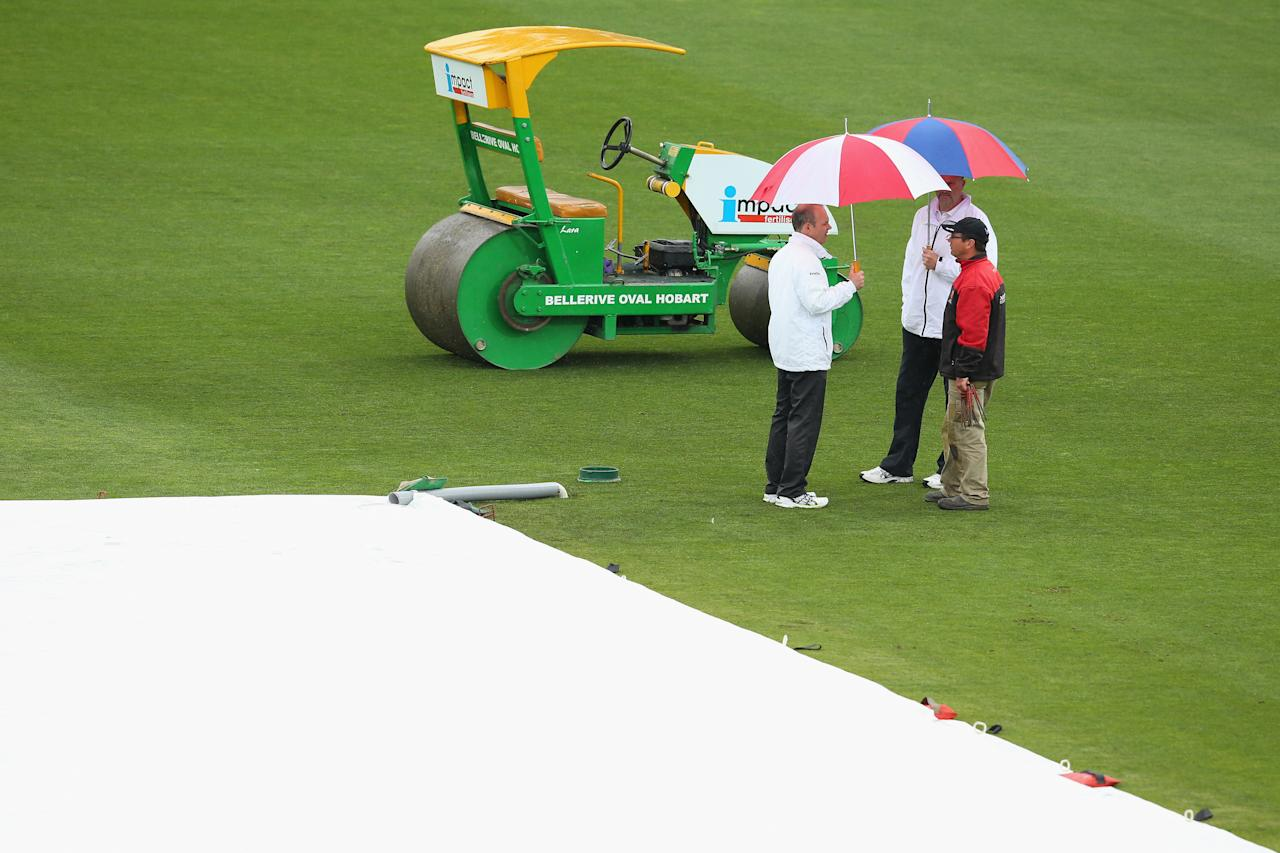 HOBART, AUSTRALIA - NOVEMBER 08: Umpires Simon Fry and Paul Wilson speak to the grounds staff  as rain delays the start of play during day three of the tour match between Australia A and England at Blundstone Arena on November 8, 2013 in Hobart, Australia.  (Photo by Mark Kolbe/Getty Images)