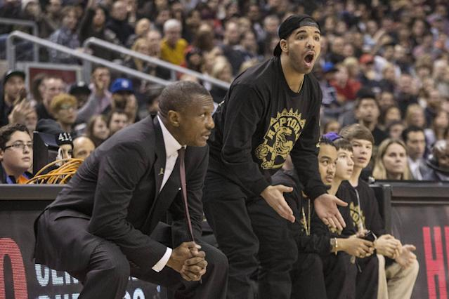Rapper Drake, center, reacts to a call as he stands with Toronto Raptors head coach Dwane Casey, left, as the Raptors face the Brooklyn Nets during the first half of an NBA basketball game, Saturday, Jan. 11, 2014 in Toronto (AP Photo/The Canadian Press, Chris Young)