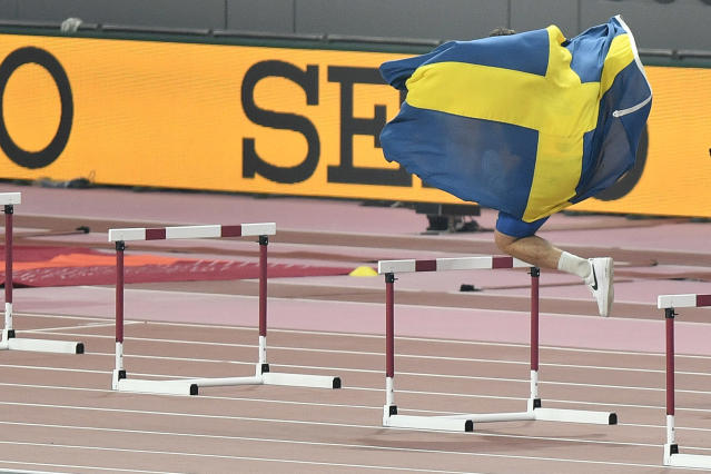 Daniel Ståhl, of Sweden, celebrates jumping over hurdles after winning the gold medal in the men's discus throw final during the World Athletics Championships in Doha, Qatar, Monday, Sept. 30, 2019. (AP Photo/Martin Meissner)