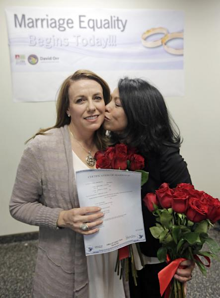 Theresa Volpe, left, and Mercedes Santos show off their Certification of Marriage after being married by Cook County Clerk David Orr, Friday, Feb. 21, 2014, in Chicago. Judge Sharon Johnson Coleman's Friday order says there is no reason to delay same-sex marriages in Illinois until June, when the state's law is set to take effect. Her finding applies only to Cook County, where Chicago is located. (AP Photo/M. Spencer Green)