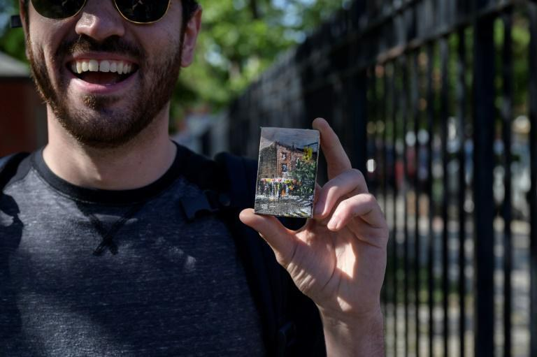 Filmmaker Zack Obid holds up the mini landscape by artist Steve Wasterval after finding it during a scavenger hunt in Greenpoint, New York on May 25, 2021