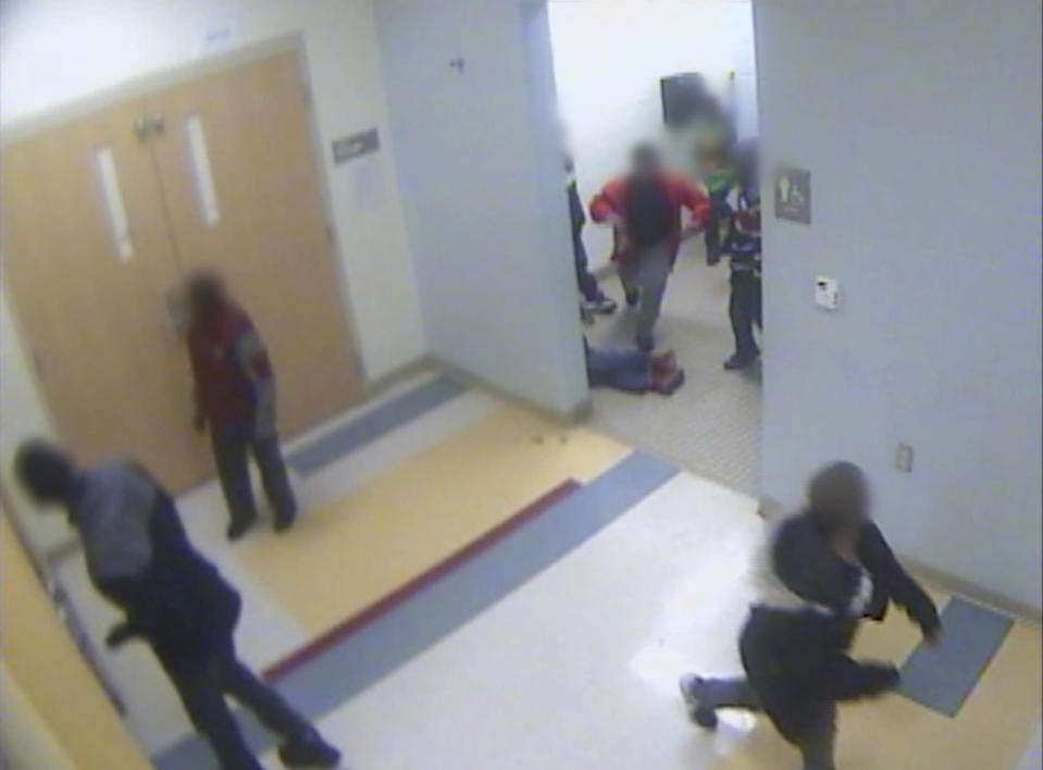FILE - In this file still image from a Jan. 24, 2017, surveillance video provided by Cincinnati Public Schools, the legs and feet of 8-year-old Gabriel Taye can be seen as he lies on the floor of a boys' bathroom after being knocked unconscious by another boy at Carson Elementary School. Two days later, Taye hanged himself with a necktie in the bedroom of his Cincinnati apartment. Taye's parents can move forward with a lawsuit against the Cincinnati school district that alleges wrongful death and other charges, a federal appeals panel ruled Tuesday, Dec. 29, 2020. (Cincinnati Public Schools via AP, File)