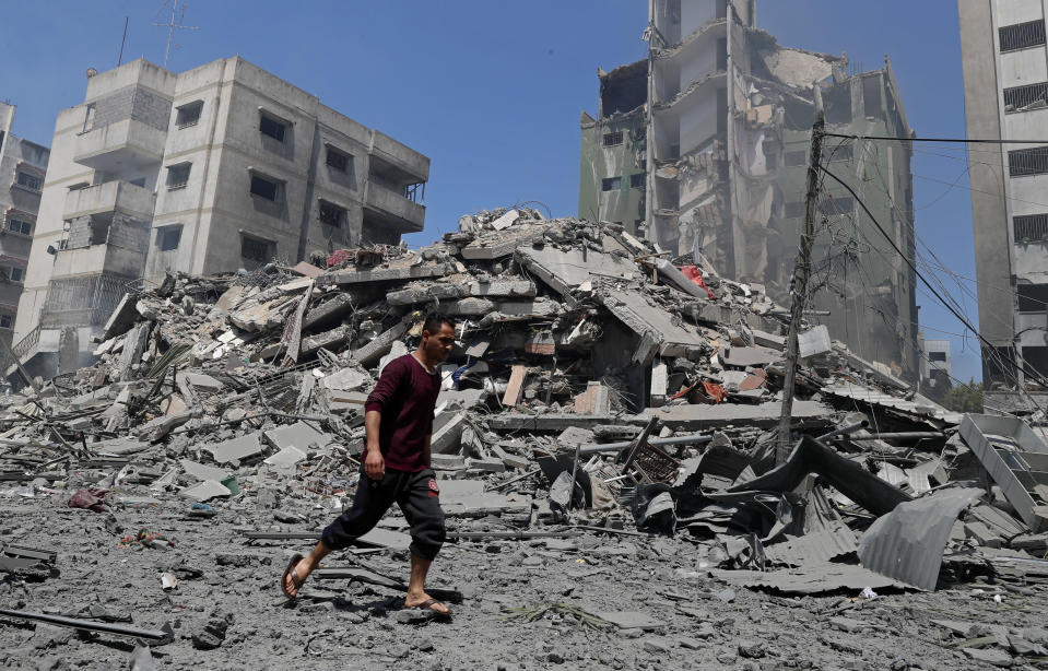A man walks past the the rubble of the Yazegi residential building that was destroyed by an Israeli airstrike, in Gaza City, Sunday, May 16, 2021. The 57-member Organization of Islamic Cooperation held an emergency virtual meeting Sunday over the situation in Gaza calling for an end to Israel's military attacks on the Gaza Strip. (AP Photo/Adel Hana)