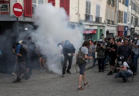 Demonstrators react after police used tear gas during a protest against G7 summit, in Bayonne