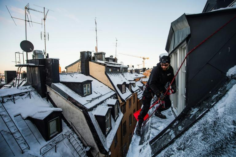 Rooftop snow remover Andrei Plian works on top of one of Stockholm's old town buildings. 'Being here on the roof and looking up at the sky, you feel that freedom,' he said