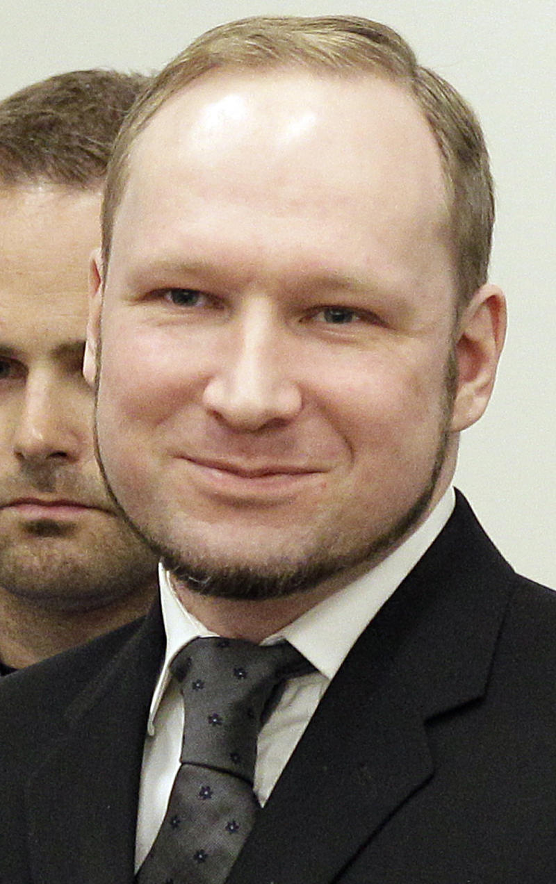 Mass murderer Anders Behring Breivik,  smiles as he arrives at the courtroom in a courthouse in Oslo  Friday Aug. 24, 2012 .  Breivik was convicted Friday of terrorism and premeditated murder for bomb and gun attacks that killed 77 people and sentenced to a special prison term that would allow authorities to keep him locked up for as long as he is considered dangerous. (AP Photo/Frank Augstein)