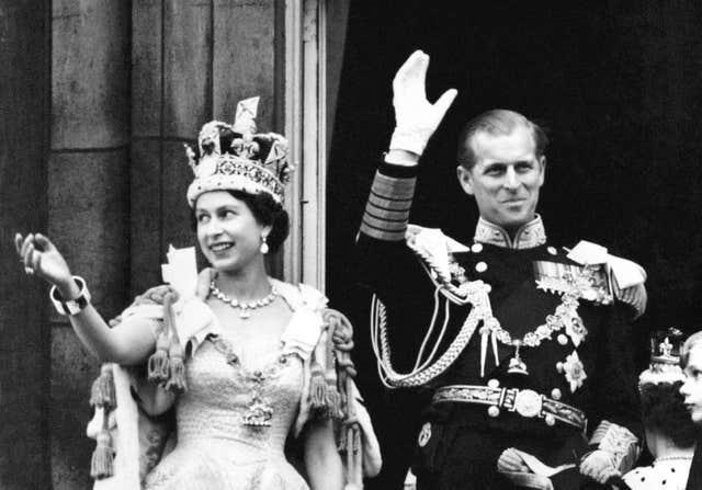 Queen Elizabeth II wearing the Imperial State Crown and the Duke of Edinburgh in uniform of Admiral of the Fleet wave from the balcony to the onlooking crowds around the gates of Buckingham Palace after the Coronation