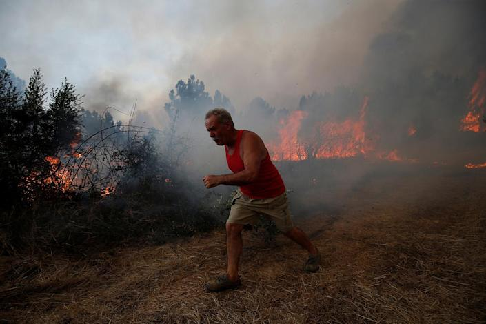 <p>A villager works to put out a forest fire in the village of Brejo Grande, near Castelo Branco, Portugal, July 25, 2017. (Rafael Marchante/Reuters) </p>