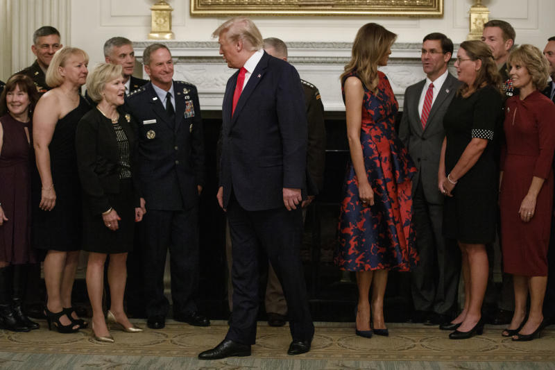 President Donald Trump and first lady Melania Trump, joined by Defense Secretary Mark Esper, and Chairman of the Joint Chiefs of Staff Gen. Mark Milley, and others, talk after posing for media during a social dinner with senior military leaders and spouses at the White House in Washington, Monday, Oct. 7, 2019. (AP Photo/Carolyn Kaster)