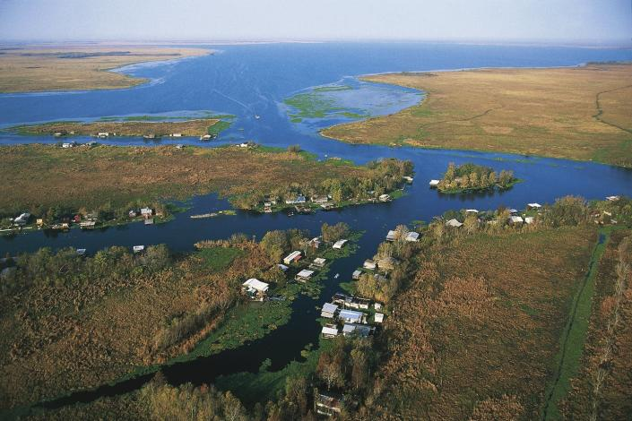 Aerial photo showing homes and covered docks lining the edges of a bayou.