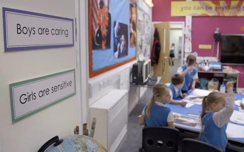 Signs that read 'Boys and caring' and 'Girls are sensitive' are placed around the classroom
