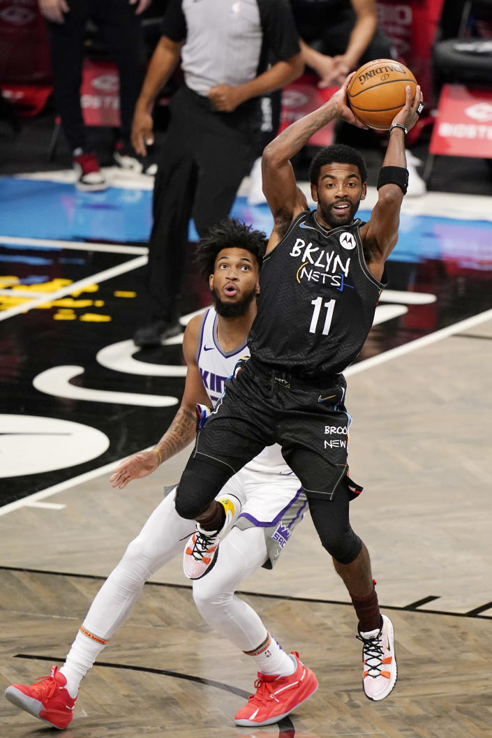 Sacramento Kings forward Marvin Bagley III, left, looks on as Brooklyn Nets guard Kyrie Irving, right, passes during the first quarter of an NBA basketball game, Tuesday, Feb. 23, 2021, in New York. (AP Photo/Kathy Willens)