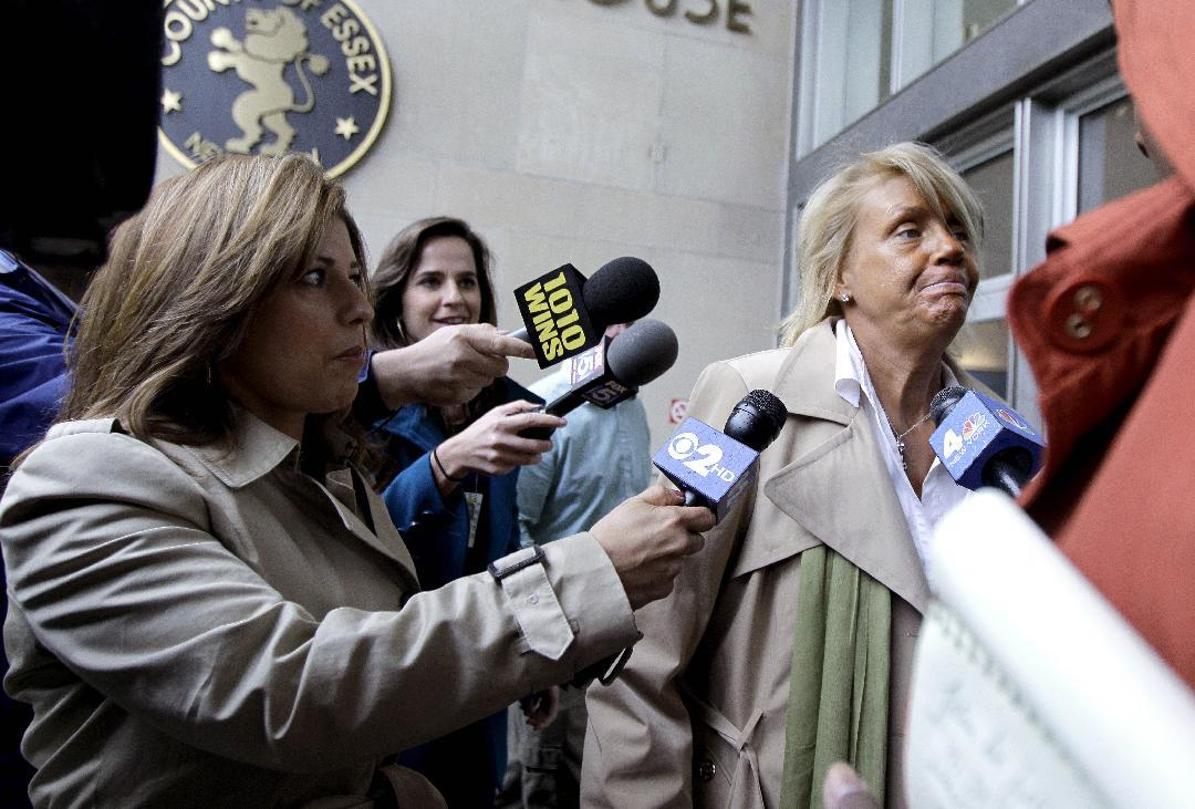 Reporters talk to Patricia Krentcil, 44, center right, as she walks out of Essex County Superior Court after court appearance on charges of child endangerment, Wednesday, May 2, 2012 in Newark, N.J. Krentcil is accused of taking her 5-year-old child into a tanning booth. Krentcil tells The Associated Press her daughter got her sunburn from being outside on a recent warm day. New Jersey state law prohibits anyone under 14 from using tanning salons.(AP Photo/Julio Cortez)
