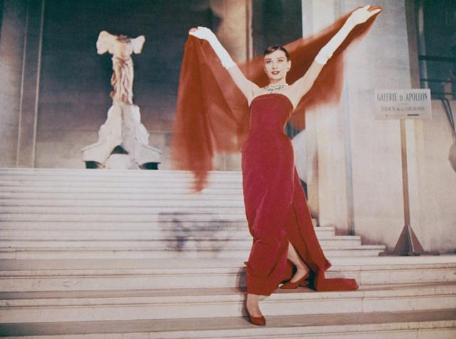 """Hepburn wearing a red dress by Givenchyin a scene from the film """"Funny Face"""" in 1957."""