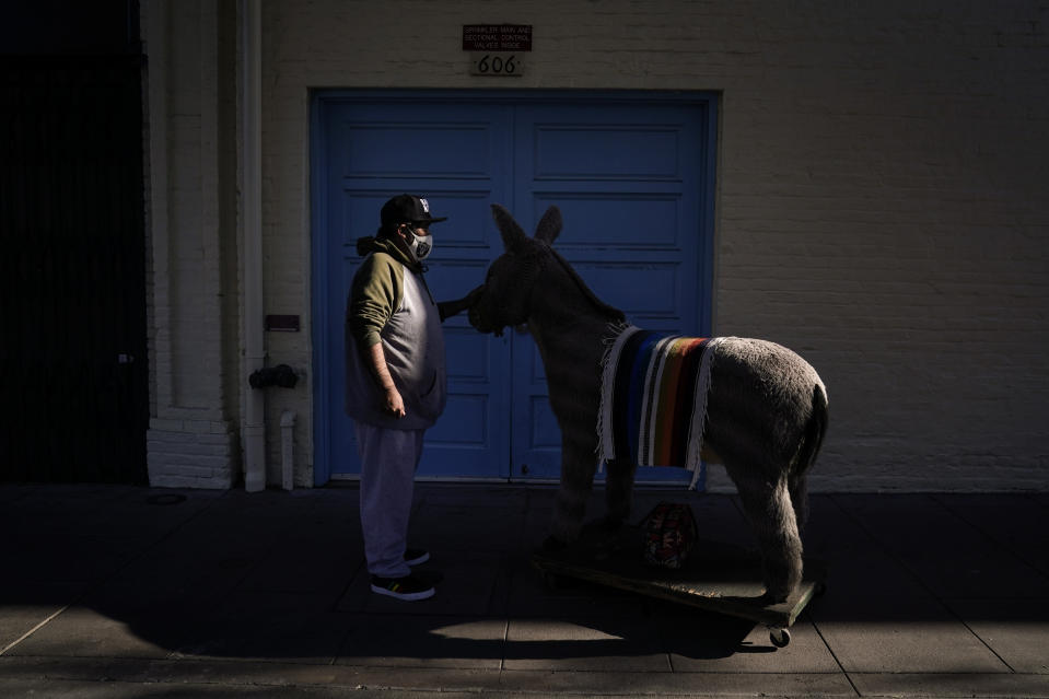 Jesus Hernandez, a merchant who owns a gift shop on Olvera Street that only opens on weekends due to the pandemic, waits for a key to store his uncle's life-size stuffed donkey, a photo prop named George, in downtown Los Angeles, Wednesday, Dec. 16, 2020. Olvera Street, known as the birthplace of Los Angeles, has been particularly hard hit by the coronavirus pandemic, with shops and restaurants closed and others barely hanging on. (AP Photo/Jae C. Hong)