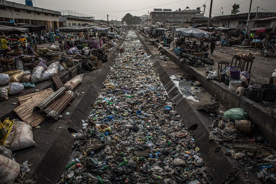 A channel filled with rubbish in between market stalls.