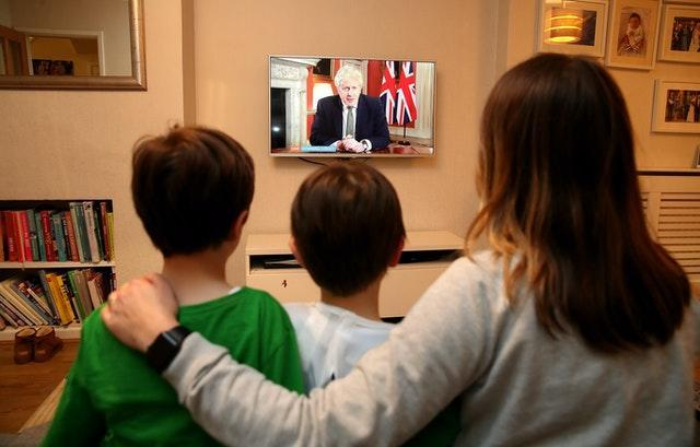 A family in Knutsford, Cheshire, watch Prime Minister Boris Johnson making a televised addres
